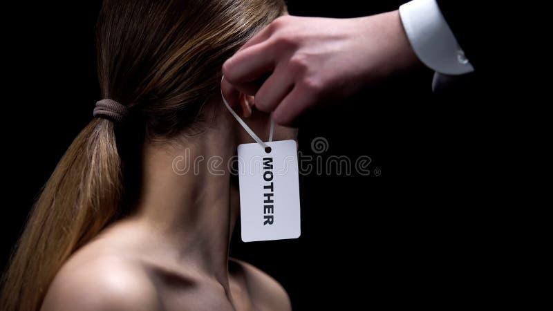 Main masculine mettant l'étiquette de mère sur l'oreille femelle, stéréotype de genre au sujet des femmes images libres de droits