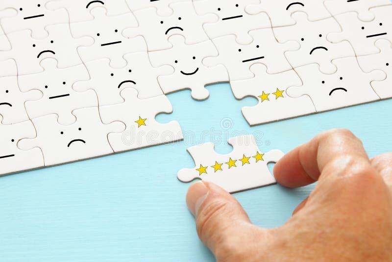 main masculine mettant le dernier morceau dans le puzzle Image de concept de fixer un but de cinq étoiles estimation d'augmentati photo stock