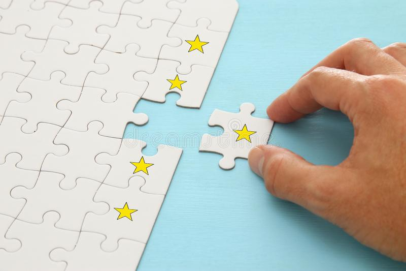 main masculine mettant le dernier morceau dans le puzzle Image de concept de fixer un but de cinq étoiles estimation d'augmentati images libres de droits