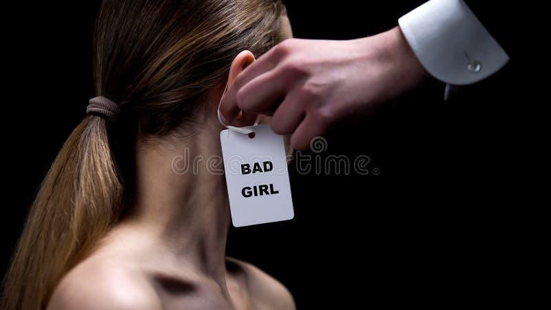 Main masculine mettant le mauvais label de fille sur l'oreille femelle, stéréotypes au sujet du comportement de femmes photographie stock