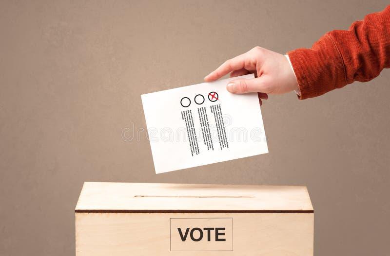 Main masculine mettant le vote dans une urne, sur le fond sale photos libres de droits