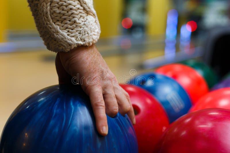 Main masculine prenant la boule de la machine de bowling photographie stock libre de droits