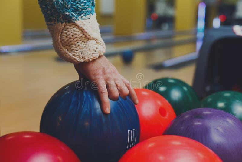 Main masculine prenant la boule de la machine de bowling image libre de droits