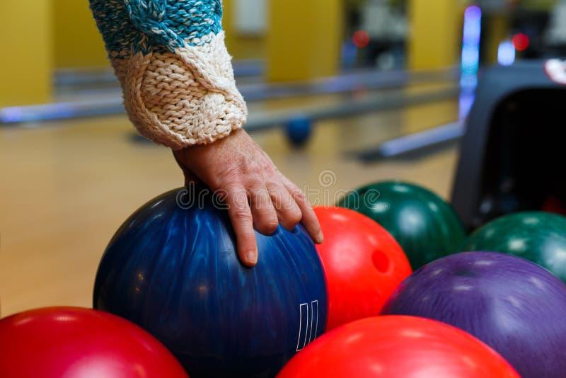 Main masculine prenant la boule de la machine de bowling photo stock