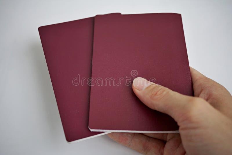 Main masculine se tenant de retour de deux passeports européens sur le fond comme symbole du déplacement international photographie stock