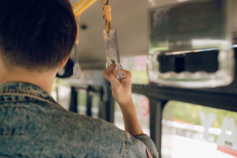 Main masculine se tenant sur une poignée d'autobus photo stock