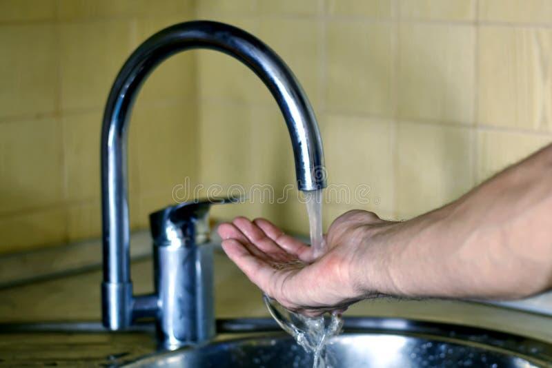 Main masculine sous l'eau courante du robinet le concept de la propreté et de la santé L'eau pure image stock