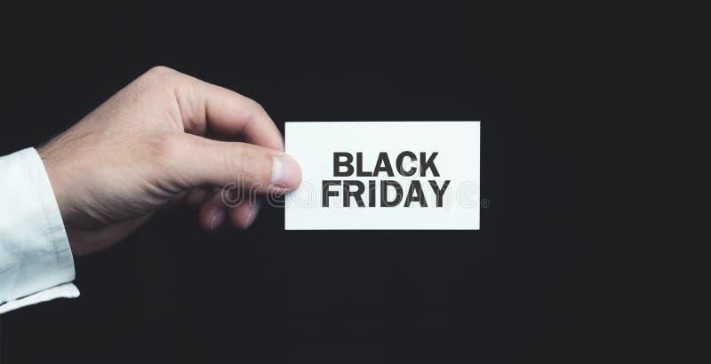Main masculine stockant le texte de Black Friday sur la carte de visite professionnelle de visite photo stock