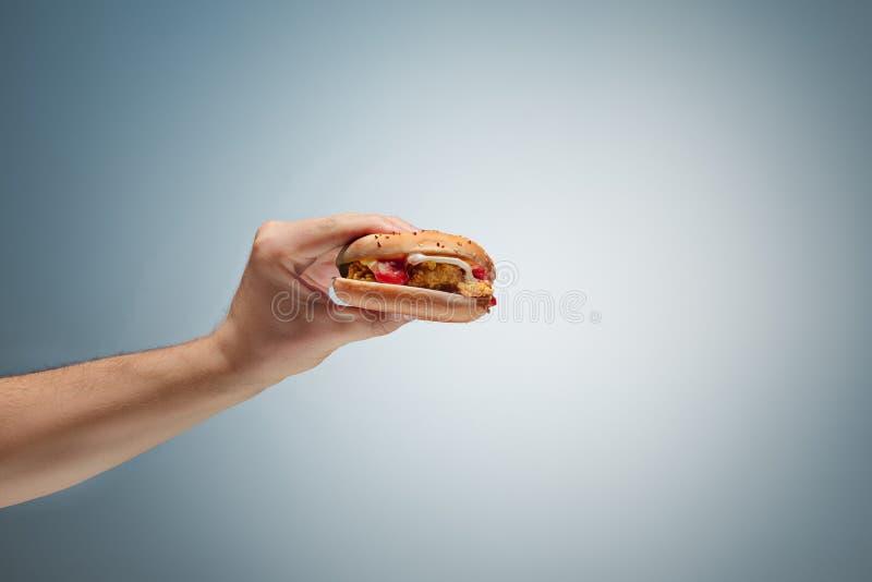 Main masculine tenant l'hamburger savoureux photographie stock