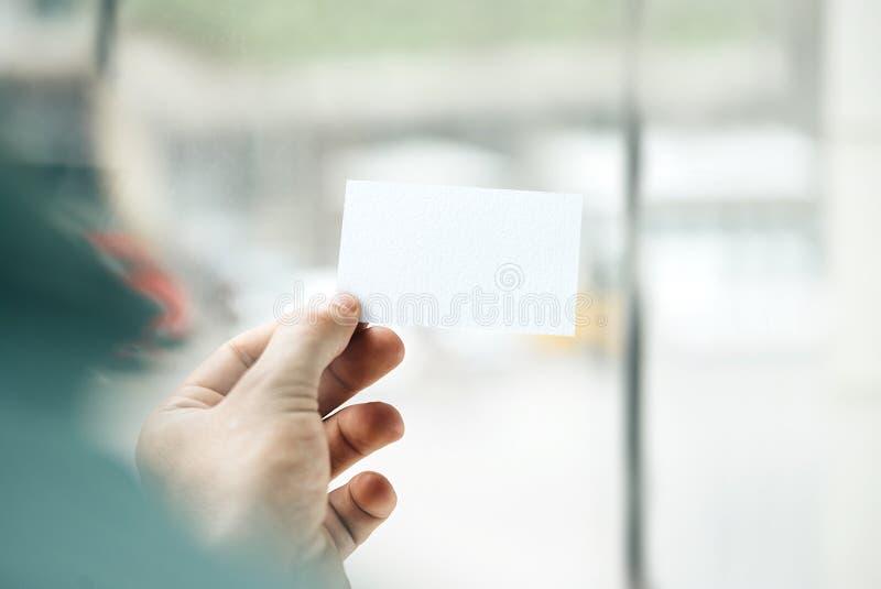 Main masculine tenant la carte de visite professionnelle de visite blanche sur photos libres de droits