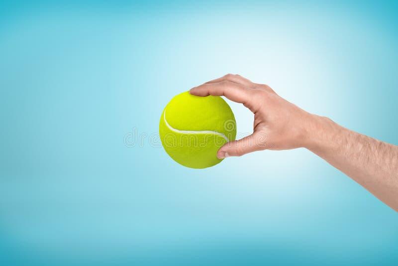 Main masculine tenant la petite balle de tennis entre les doigts sur le fond bleu photo stock