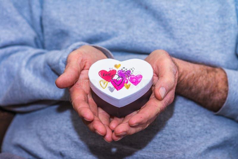Main masculine tenant le boîte-cadeau en forme de coeur photographie stock