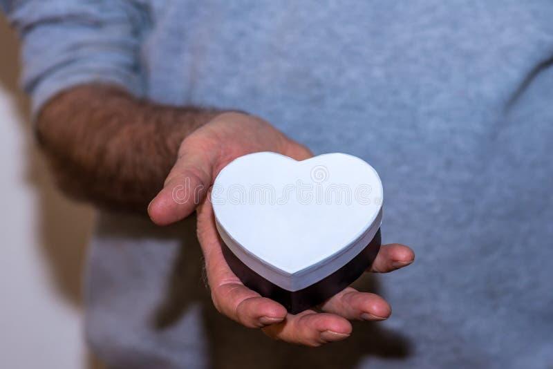 Main masculine tenant le boîte-cadeau en forme de coeur blanc images stock
