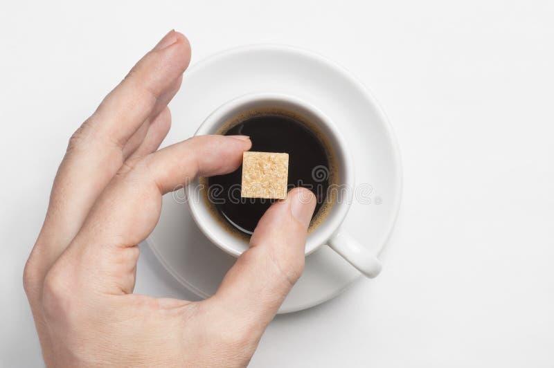 Main masculine tenant le cube en sucre de canne au-dessus de la tasse de café noir contre la vue supérieure de fond blanc avec l' images libres de droits