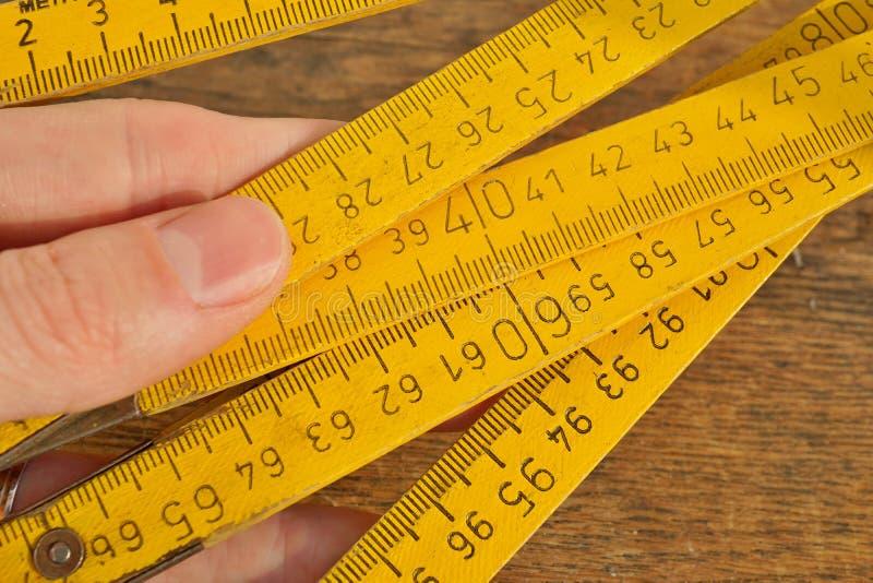 Main masculine tenant le mètre se pliant jaune sur le fond en bois comme symbole de précision image libre de droits