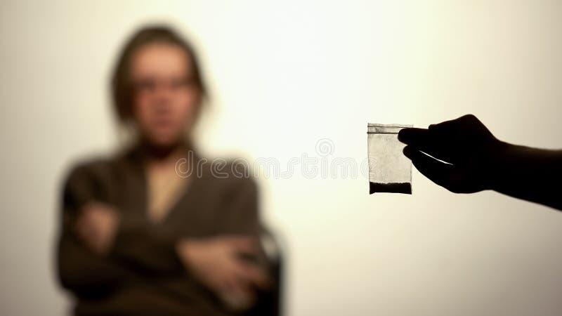 Main masculine tenant le paquet de cocaïne, toxicomanie, puissance de volonté, programme de réadaptation photographie stock