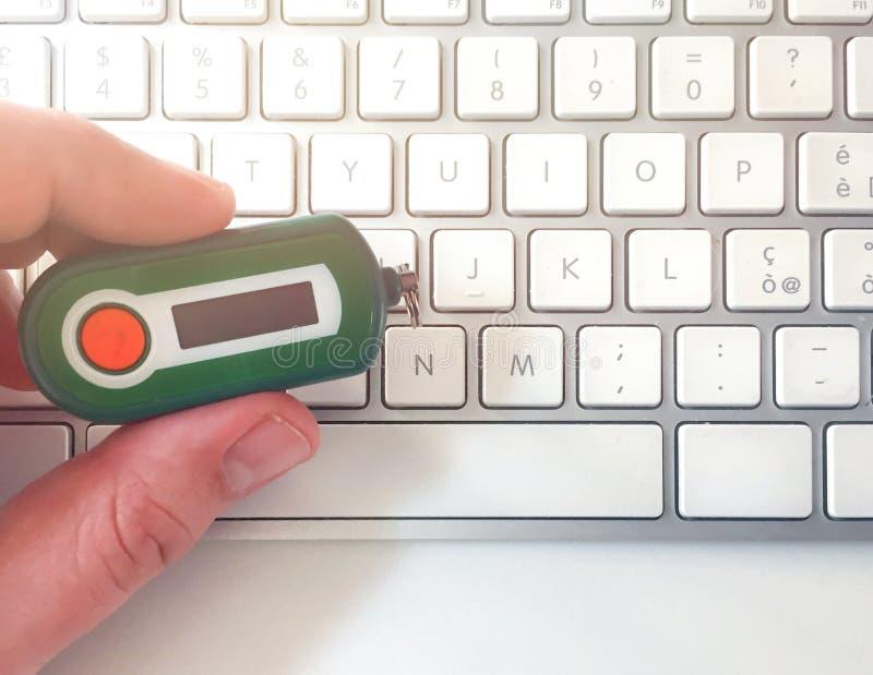 Main masculine tenant un générateur de code de banque sur un clavier d'ordinateur blanc image stock