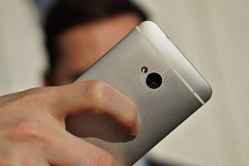 Main masculine tenant un téléphone mobile intelligent argenté tout en prenant le selfie photographie stock