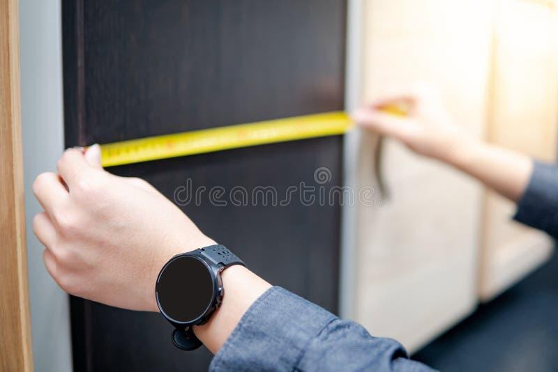 Main masculine utilisant le ruban métrique sur des matériaux d'armoire photos stock