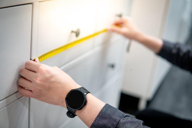 Main masculine utilisant le ruban métrique sur le tiroir d'armoire photographie stock