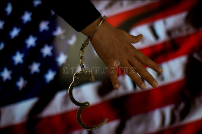 Main menottée devant le drapeau de pays Concept de crime photos stock