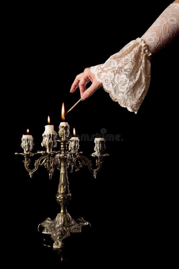 Main mettant à feu des bougies photographie stock