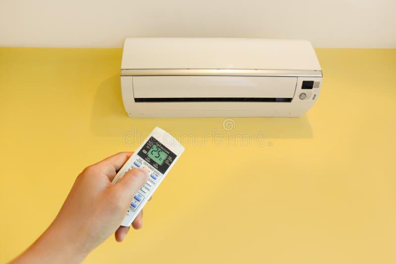 Main mettant en marche la climatisation à la maison photo stock