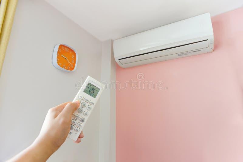 Main mettant en marche la climatisation à la maison photo libre de droits
