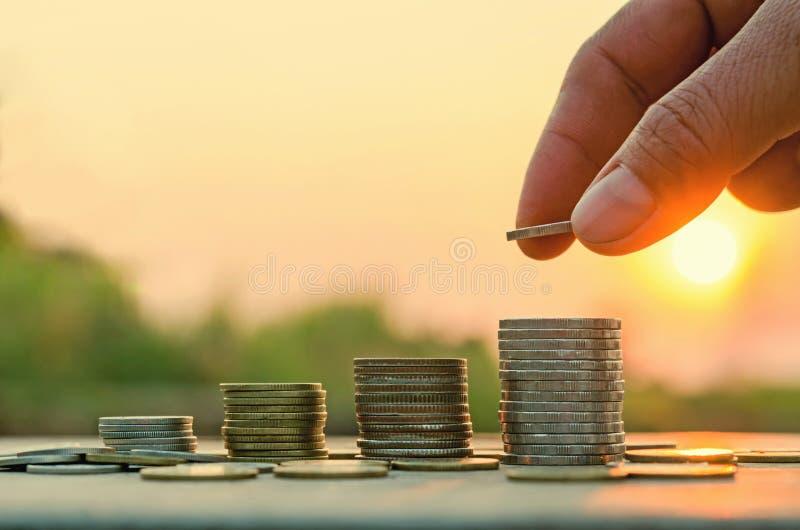 Main mettant la pièce de monnaie sur la pile de pièces de monnaie photo libre de droits