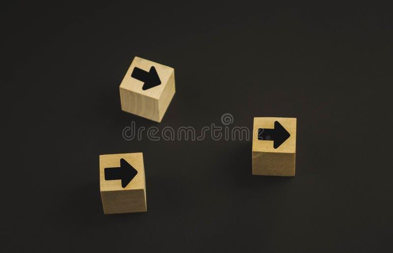 Main mettant le bloc en bois de cube sur les blocs en bois de pyramide supérieure avec les flèches rouges faisant face vis-à-vis  photo libre de droits