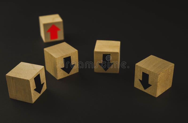 Main mettant le bloc en bois de cube sur les blocs en bois de pyramide supérieure avec les flèches rouges faisant face vis-à-vis  photographie stock