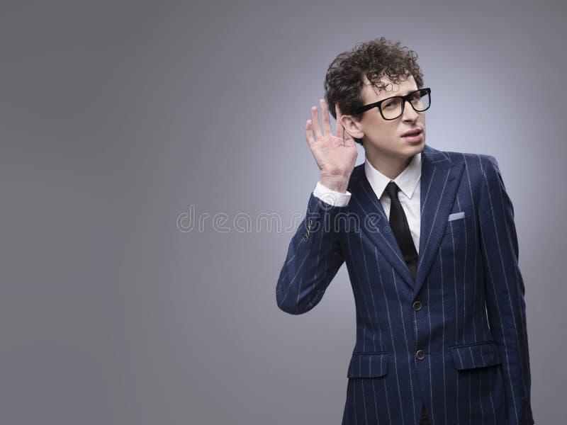 Main mettante en forme de tasse d'homme derrière l'oreille photo libre de droits