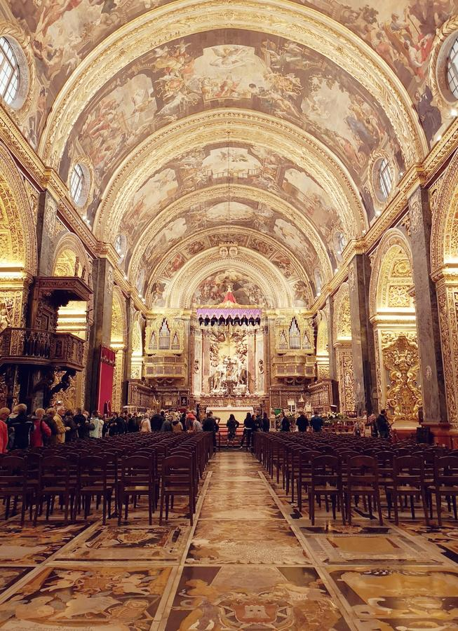 The main nave altar and ceiling in the St John's Co Cathedral, Valletta, Malta. The main nave with arched ceiling painted by Mattia Preti and gilded columns royalty free stock photography