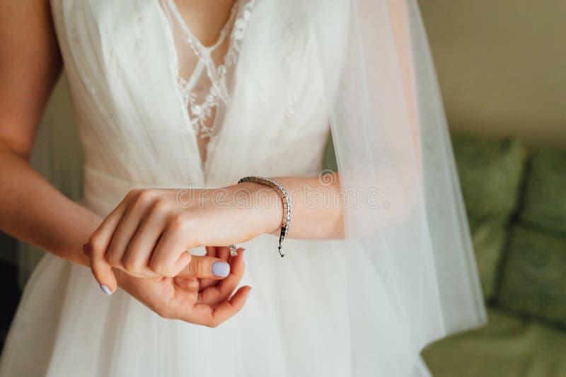 Main nuptiale élégante avec le bracelet argenté Préparation nuptiale de matin avec les accessoires élégants photo libre de droits