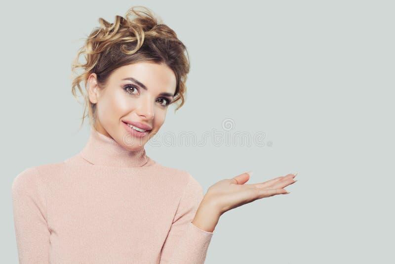 Main ouverte de Woman Holding Empty de modèle heureux avec l'espace de copie et sourire sur le fond blanc photos libres de droits
