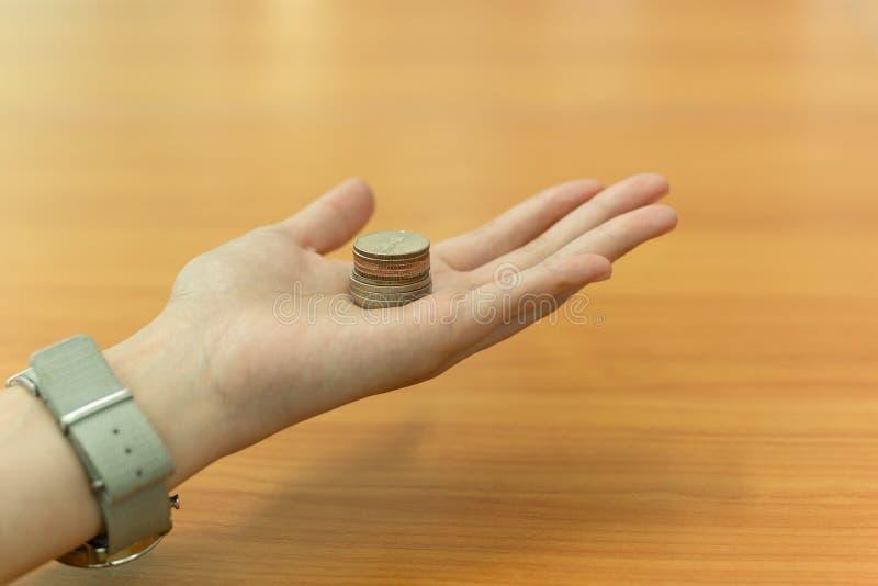 Main ouverte tenant la pièce de monnaie de Thia sur la table en bois à l'arrière-plan photographie stock