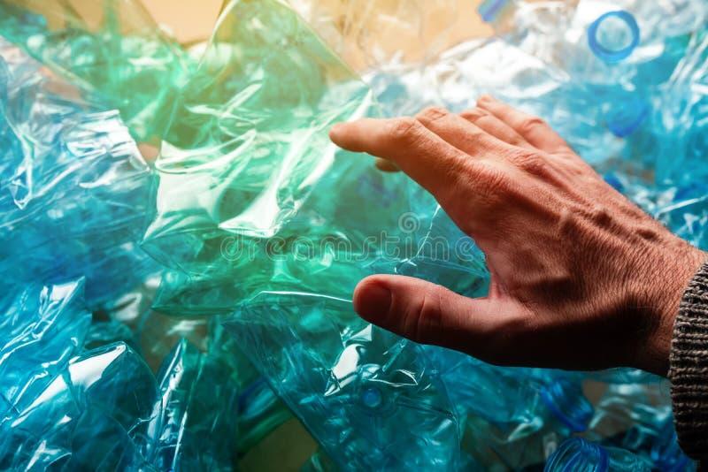 Main parmi les bouteilles en plastique écrasées photographie stock libre de droits
