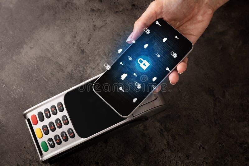 Main payant avec le téléphone portable sur la position image stock