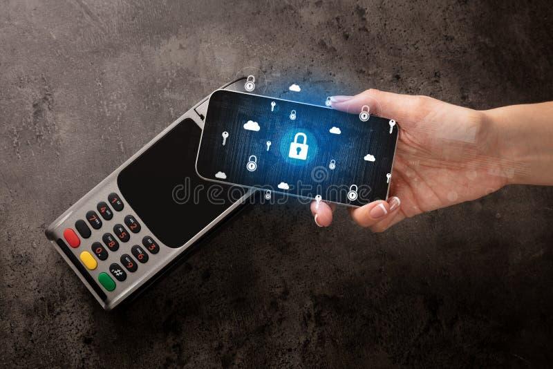 Main payant avec le t?l?phone portable sur la position image stock