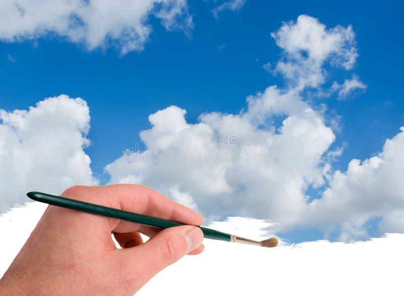 Main peignant le ciel bleu images stock