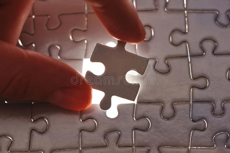 Main plaçant la partie manquante de puzzle photo libre de droits
