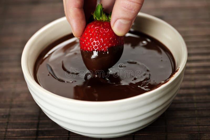 Main plongeant la fraise en chocolat image libre de droits