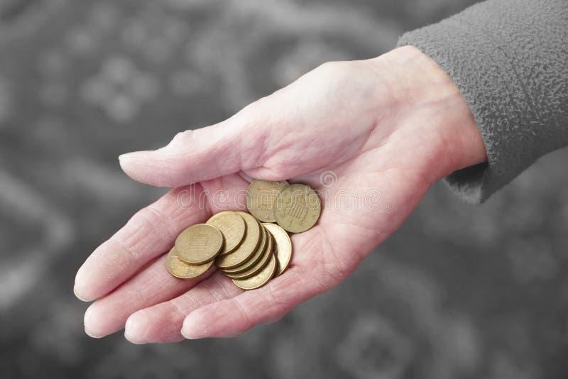 Main pluse âgé tenant l'épargne de cuivre de pauvreté de pension de penny de pièces de monnaie de changement lâche d'argent liqui photo libre de droits