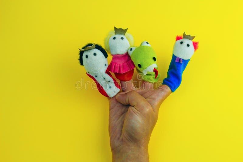 main portant 4 marionnettes de doigt - roi, prince, princesse et dragon image libre de droits