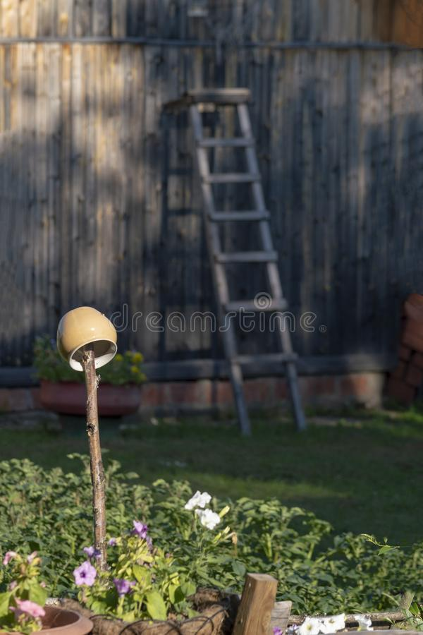 The main pot dries on a stick in the courtyard of a private house in Siberia, and in the background is a wooden staircase. royalty free stock photography