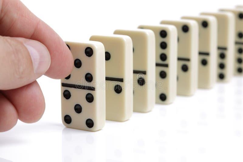 Main poussant les dominos blancs image stock