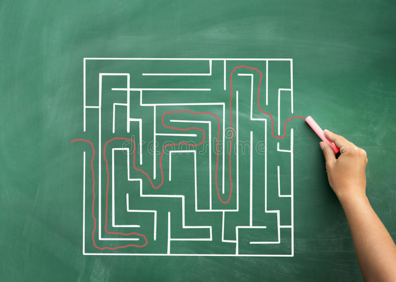 Main résolvant le labyrinthe dessiné sur le tableau noir images stock