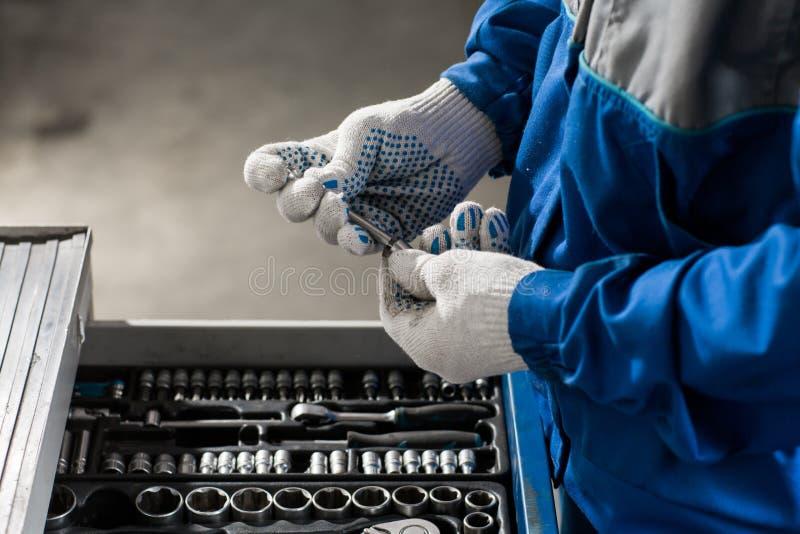 Main retenant la clé Service d'atelier de réparations automatiques image stock