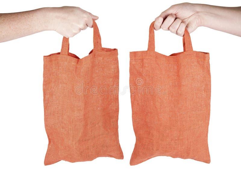 Main retenant le sac à provisions réutilisable de tissu orange images stock