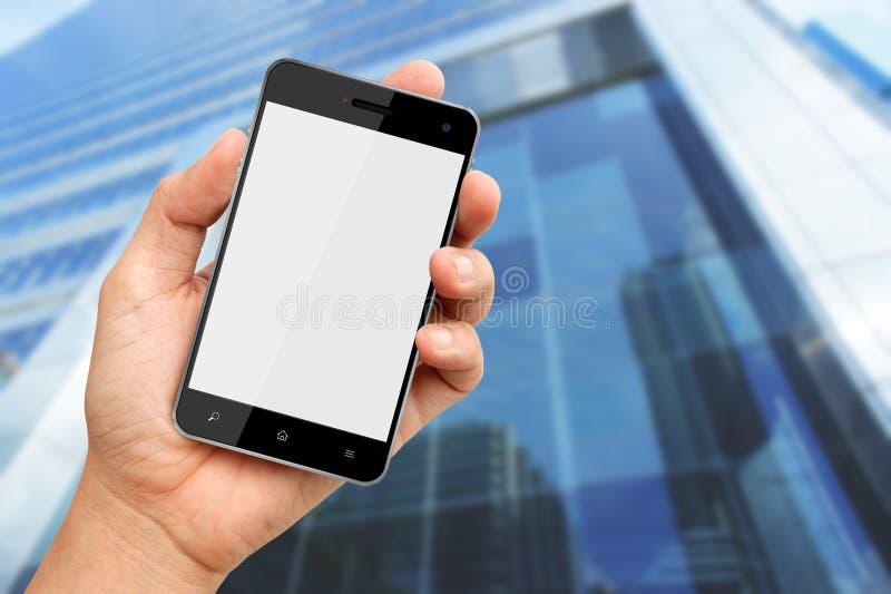 Main retenant le téléphone intelligent avec le fond de construction images stock